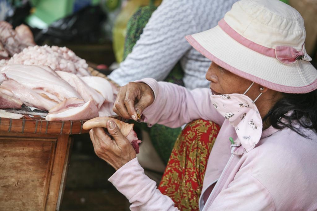 Vietnamská trhovkyně v Chau Doc s láskou holí prasečí ocásek. Asi aby se líp prodával.