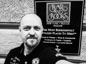 Tomáš Hájek (My Lost Hat) před cedulí Bar and Books v Praze.