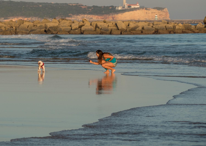 Dívka se psem na pláži pobřeží Algarve.