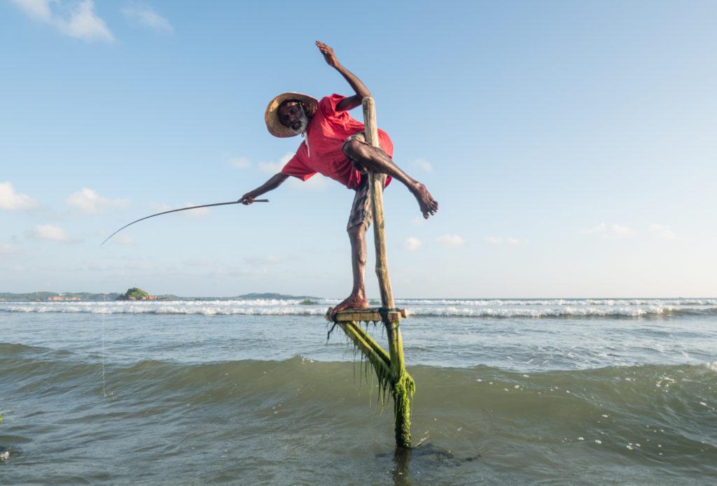 Rybář na kůlu na ostrově Ceylon.