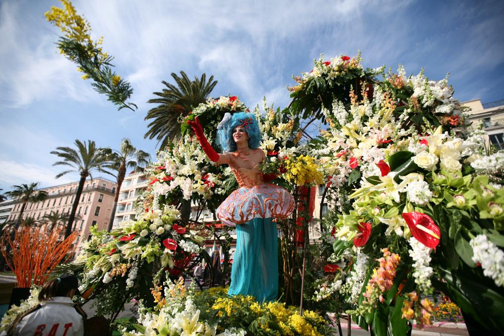 Květinové vozy jsou přeplněné kytkami, které kársné dívky házejí návštěvníkům.