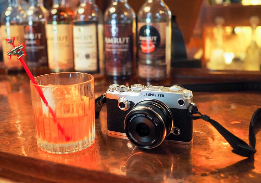 Fotoaparát Olympus PEN-F položený na baru se sklenkou japonské whisky.