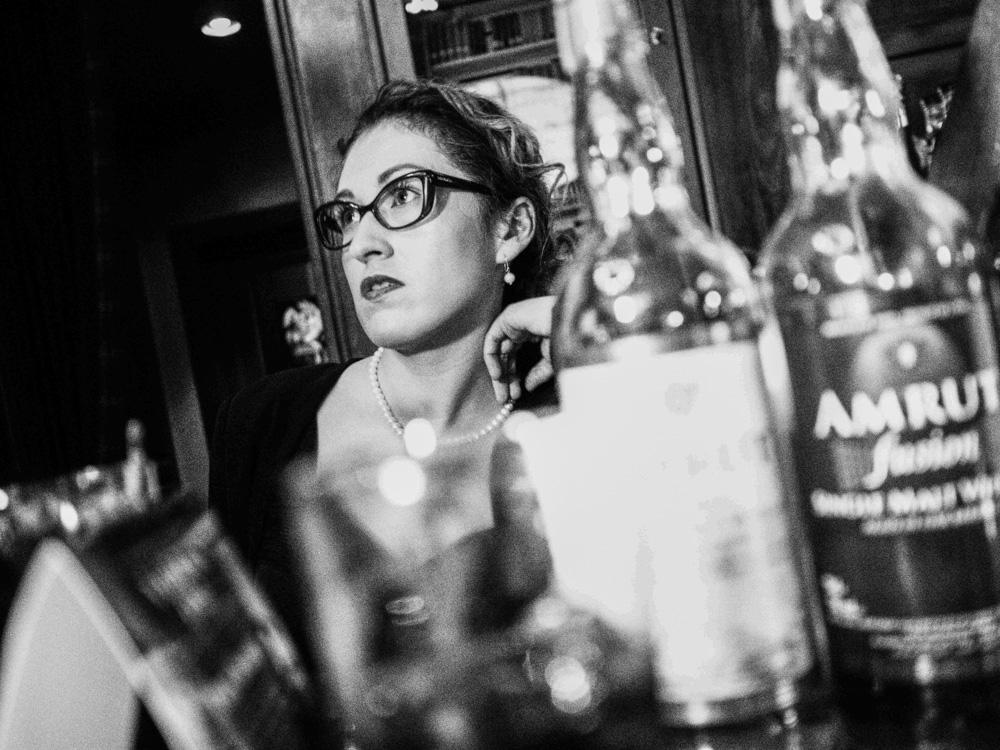 Černobílá fotografie dívky vyfocená za barem.