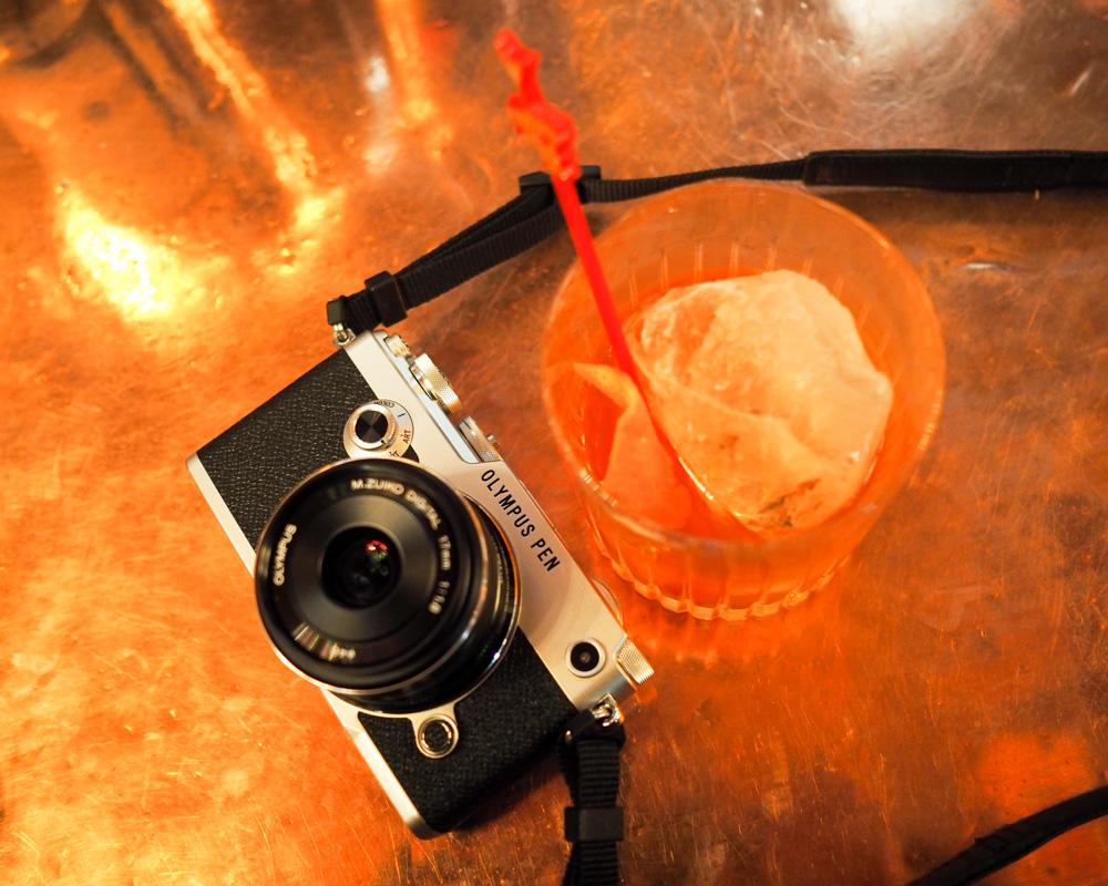Fotografie fotoaparátu Olympus PEN-F a sklenice japonské whisky.