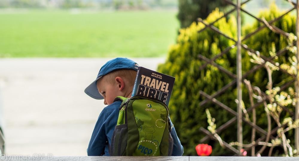 Kniha Travel Bible v batůžku na zádech malého kluka.